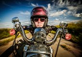 Funny Biker girl in sunglasses and leather jacket racing on the road (fisheye lens)