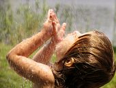 stock photo of dancing rain  - Child playing in the rain and licking rain drops - JPG