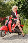 Woman posing in fashionable summer dress on a scooter