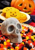 closeup of a plate with Halloween candies and a skull, and some pumpkin-shaped cookies with scary or