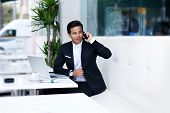 Attractive and handsome businessman using mobile phone, wealthy man talking on the smartphone