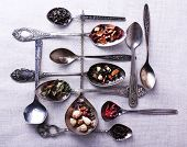 Tea in metal spoons on fabric background