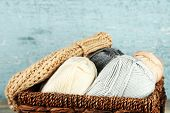 Knitting yarn and cap in basket, on wooden background