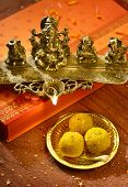 A metallic Ganesha statue lamp with Indian sweets.