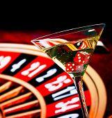 stock photo of roulette table  - red dice in the cocktail glass in front of roulette wheel casino series - JPG