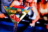 Red Dice In The Cocktail Glass In Front Of Gambling Table