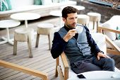 Rich businessman in grey suit drink coffee serious looking away