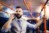foto of tram  - Handsome hipster modern man calling by mobile phone in tram in night - JPG