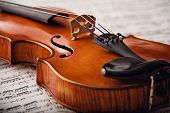 stock photo of violin  - Detail of an ancient rare violin on music notes - JPG