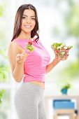 Vertical shot of an attractive woman holding a salad at home