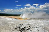 Geyser Basin Erupts Against Blue Sky