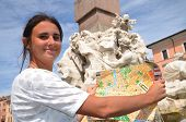 beautiful attractive brunette tourist girl holding a map on Piazza Navona in Rome, Italy