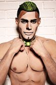 image of beast-man  - fashion studio photo of sexy muscular man with bright painted face for Halloween party - JPG