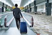 picture of escalator  - Rear view of businessman carrying luggage walk toward escalator in airport hall - JPG