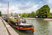 Old Pleasure Boats Stand Moored, Seine River Coast In Paris, France