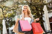 Young Blond Woman With Shopping Bags Calling Through A Mobile Phone.