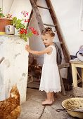 Happy little girl by the old farmhouse