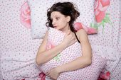 Frightened Young Girl Hugging A Pillow While Lying In Bed