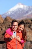 Selfie couple hiking in beautiful nature with smartphone. Happy couple walking enjoying view and taking pictures with smart phone. Man and woman by Volcano Teide on Tenerife, Canary Islands.