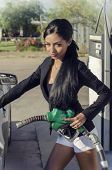 Beautiful elegant young woman fueling pumping gas