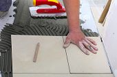 Construction Worker Is Tiling At Home, Tile Floor Adhesive