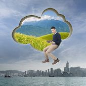 Cloud concept with man sit at a cloud shaped wall and using tablet.