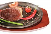 meat savory : platter of grilled beefsteak served with hot cayenne peppers red tomato green chives o