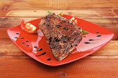 roast meat shoulder on red with tomatoes chives and green lettuce wooden table