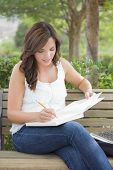 Attractive Young Adult Female Student on Bench Outdoors with Books and Pencil.