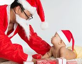 Asian santa claus with baby boy, many Christmas presents on floor.