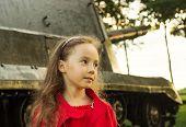 vintage portrait of little girl near military tank