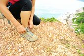 young woman hiker tying shoelaces on seaside trail
