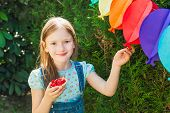 Adorable little girl eating strawberry cake on a birthday party on a nice sunny summer day