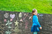 Adorable little girl drawing with chalk outdoors