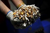 picture of smuggling  - Hands of a man holding a heap of destroyed counterfeited cigarettes