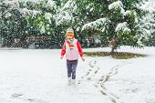 Winter portrait of a cute little girl under the snowfall, wearing red pullover, colorful hat and sca