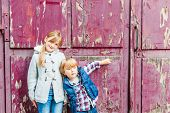 Portrait of two adorable kids outdoors on a street, against old door
