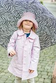 Outdoor portrait of a cute little girl with zebra pattern umbrella, wearing pink rain coat and hat