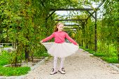 Adorable little girl spinning around in a beautiful park on a nice sunny day, wearing tutu skirt, b