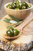image of kalamata olives  - Wooden spoon and bowl with green olives on a cutting board on the table of the kitchen - JPG