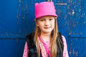 Fashion portrait of a cute little girl in a pink hat with cat ears