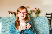 Indoor portrait of a cute little girl resting on a sofa with a cup of tea