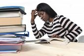 foto of exams  - young stressed black African American ethnicity student girl studying pile of books on library desk preparing exam in stress feeling tired and overwhelmed in youth education concept - JPG