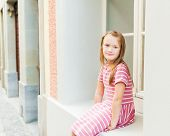Adorable little girl resting outdoors, sitting by the window