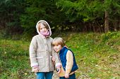 Two adorable kids playing in a forest on a cold weather
