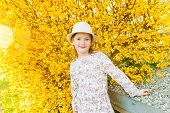 Spring portrait of adorable little girl in a white hat against yellow forsythia flowers