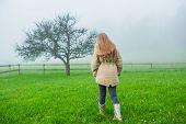 foto of girl walking away  - Outdoor portrait of a cute little girl in a garden on a foggy day - JPG
