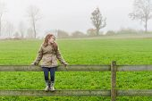 Cute little girl sitting on a fence in a countryside on a cold foggy day