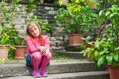 Cute little girl resting in a botanical garden on a nice day
