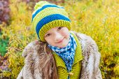 Close up portrait of a cute little girl in winter hat against autumn leaves